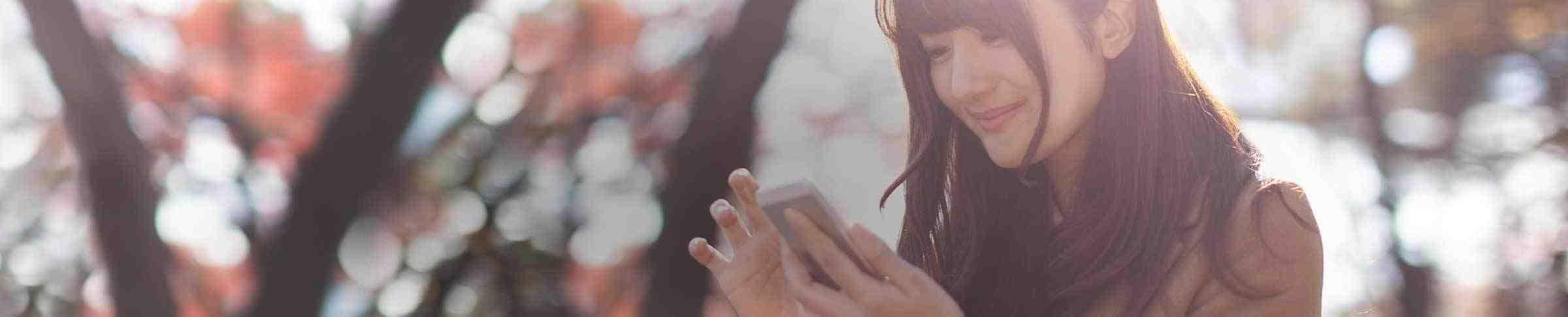 Eine junge Frau schaut auf ihr Mobiltelefon