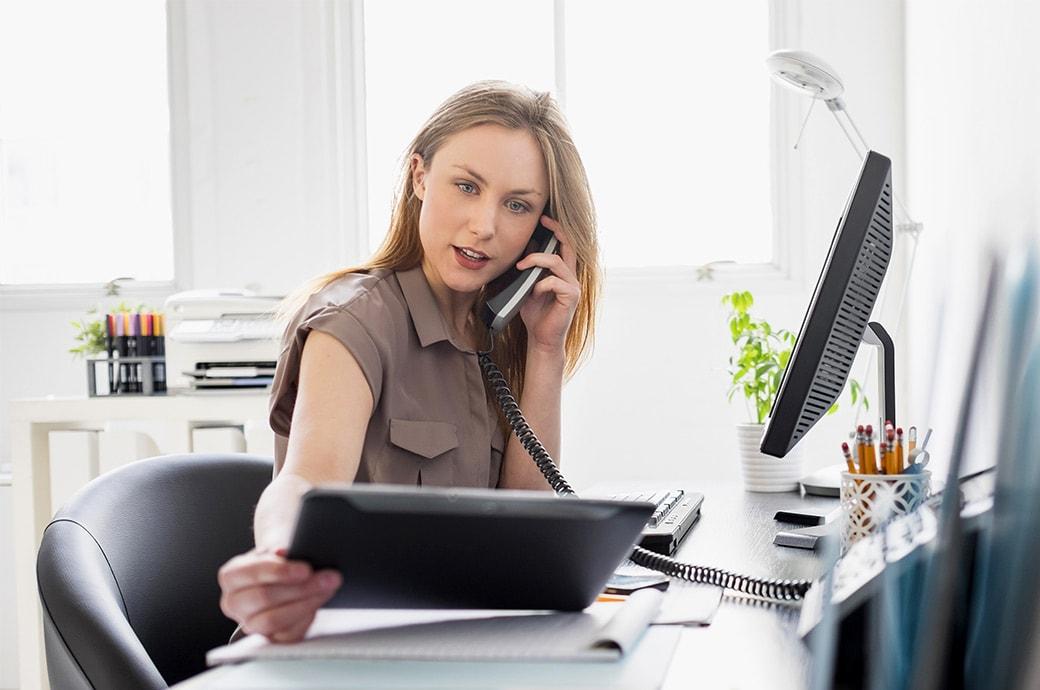 Eine Frau sitzt im Büro am Schreibtisch und schaut auf ein Tablet während sie telefoniert.