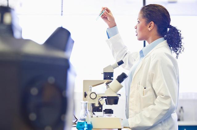 Ärztin schaut in einem Labor in ein Mikroskop.