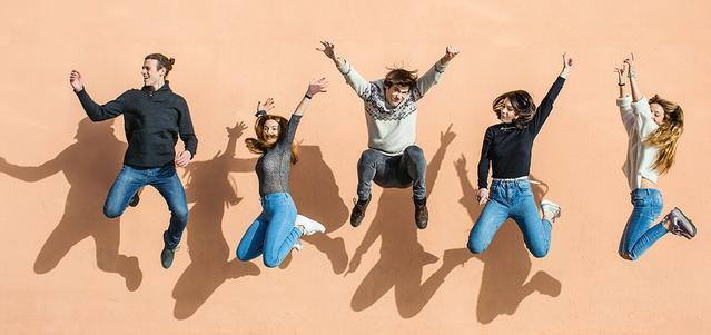 Un groupe d'amis sautant en l'air, riant et souriant.