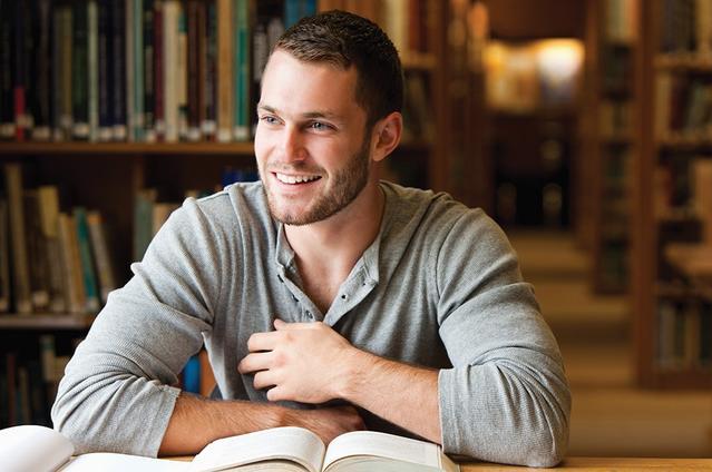 Ein Mann in einer Bibliothek mit dem Büchern vor sich auf dem Tisch.