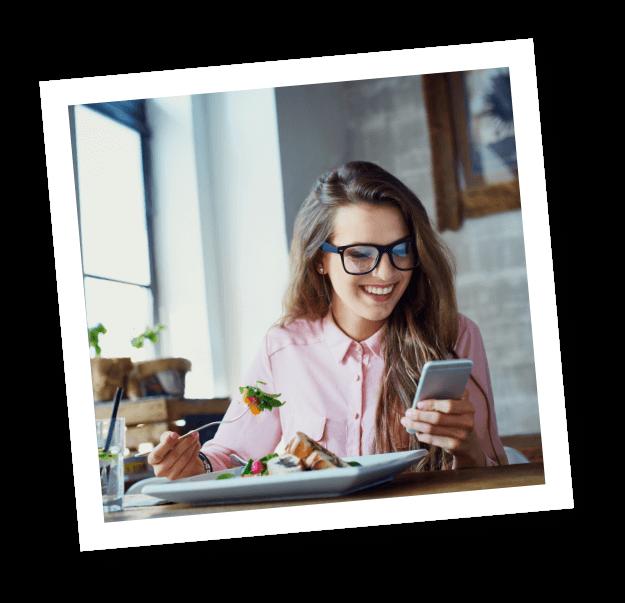 Ein Mädchen mit Brille liest in der Mittagspause auf ihrem Handy