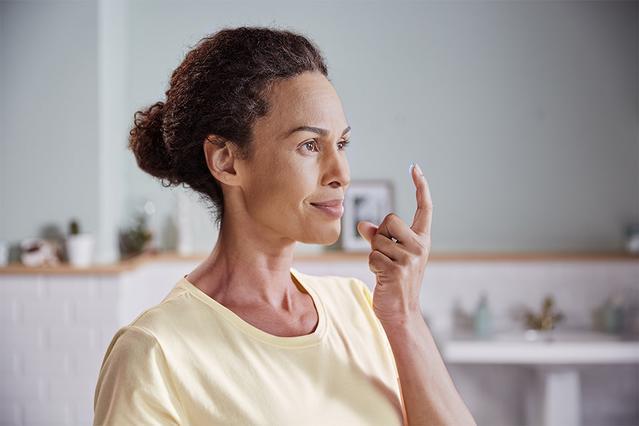 Darstellung einer Frau, die sich im Badezimmer ihre Kontaktlinsen aufsetzt