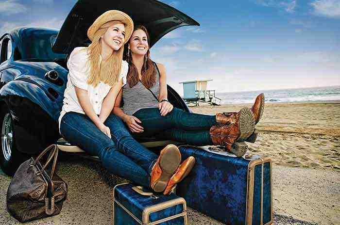 Zwei Frauen sitzen im Kofferraum ihres Autos am Strand und sind bereit ihre Ferien zu beginnen.