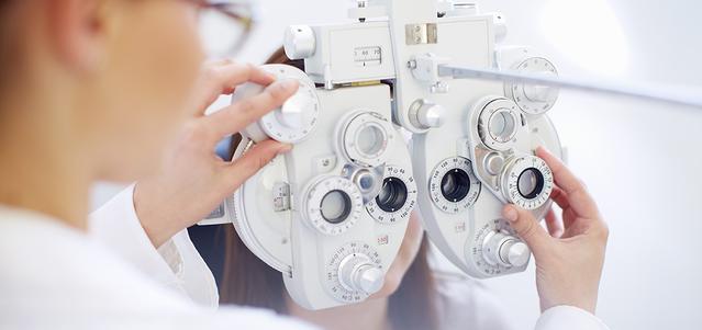 Image d'un opticien ajustant l'appareil de contrôle de la vision.