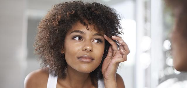 Junge Frau betrachtet ihre Augen im Spiegel.