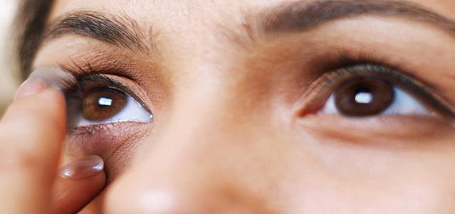 Gros plan d'une jeune femme qui met des lentilles de contact.