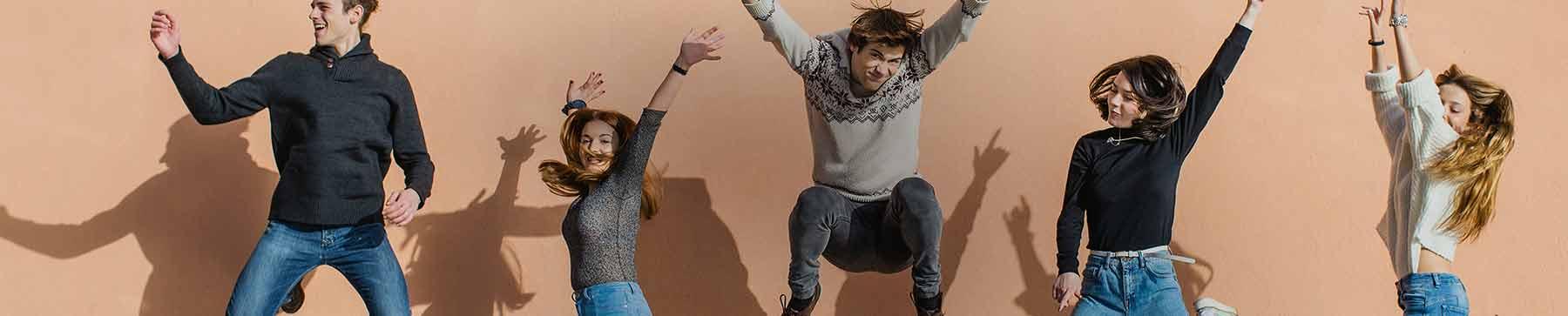 Une photo parfaitement cadencée d'un groupe d'amis sautant en l'air avec les mains en l'air