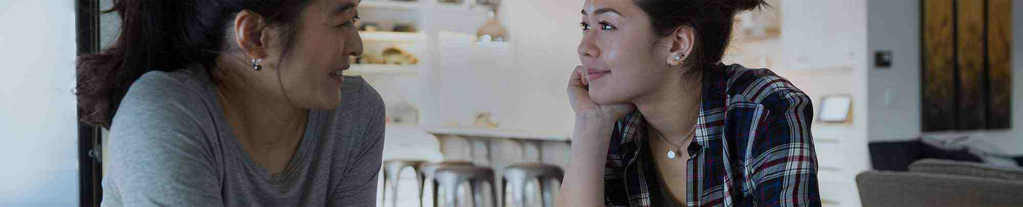 Eine junge Frau spricht mit ihrer Mutter in der Küche.