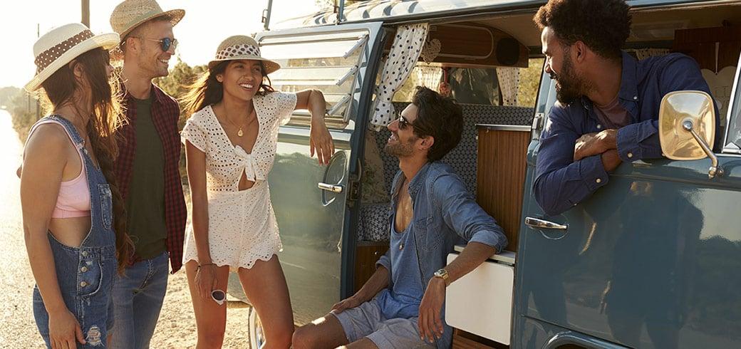 Eine Gruppe von Freunden unterhält sich mit anderen an deren Van in der Sonne