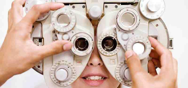 Ein Optiker justiert ein Messgerät durch das eine junge Frau schaut